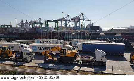 Tis Cargo Port Berth With Heavy Machinery And Maersk Container Trucks. Jcb Digger On Trailer. Indust