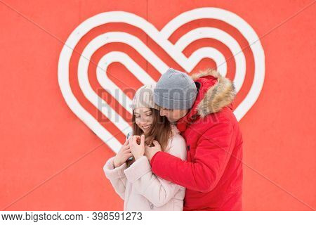Young Couple Hugging In The City Near Big Heart On The Wall. Valentine Day