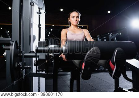 View Of Sportswoman In Pink Top And Black Leggings Training In Gym