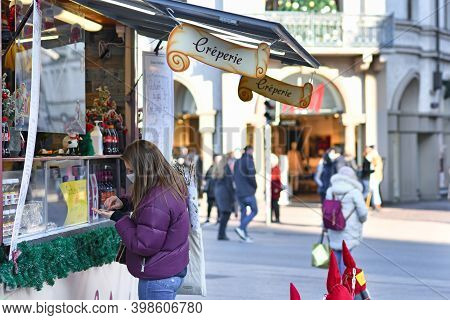 Heidelberg, Germany - December 2020: Woman With Face Mask Buying Food At Crepe Christmas Market Boot