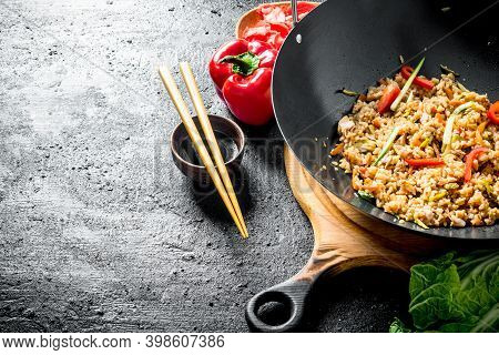 Chinese Wok. Asian Rice With Beef In A Wok Pan. On Black Rustic Background