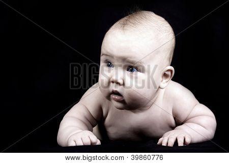 Four months baby on the dark background