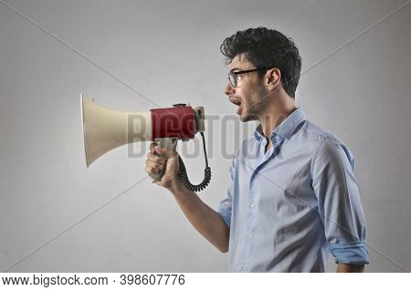 young man yells with a megaphone