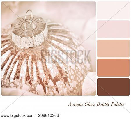 Antique glass Christmas tree bauble in delicate tones. In a colour palette with complimentary colour swatches.