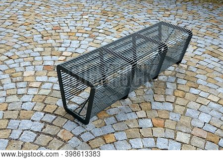Bench Without Backrest Made Of Metal Rods. Lattice Transparent Placed On Gypsum Cobblestone Paving T