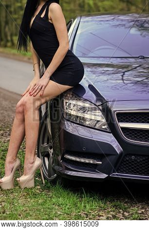 Provocative Automotive Aphrodisia. Sexy Female Sit At Car Bumper. Fashion Model With Sexy Curves. Ca