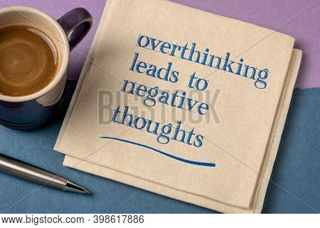Overthinking leads to negative thoughts - handwriting on a napkin with a cup of coffee, procrastination, mindset and personal development concept