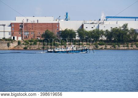 Industrial Landscape With A Factory On The Banks Of The River, Along Which A Tugboat Floats