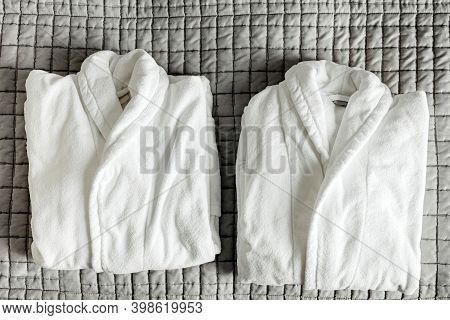 Two Folded White Bathrobe On Hotel Bed Blanket. Cotton Bath Robe For Couple In Spa. Fluffy Massage C