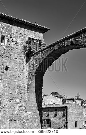 Historic Tenement House And Fragment Of An Ancient Stone Aqueduct In Pitigliano, Italy, Monochrome