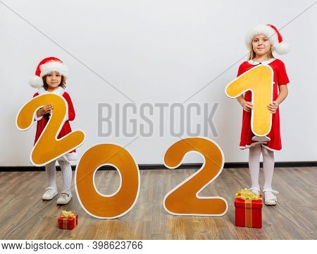 Two Girls In Santa's Helper Costumes Stand With Big New Year Numbers On A White Background