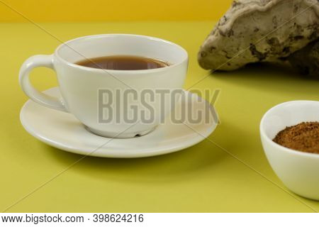 Healing Tea, Coffee And Pieces Of Birch Chaga In A White Cup On A Yellow Background. Naturopathy. Al