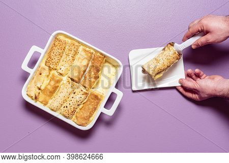 Man Hands Taking With A Spatula Stuffed Crepes From The Tray. French Pancakes Roll Filled With Sweet