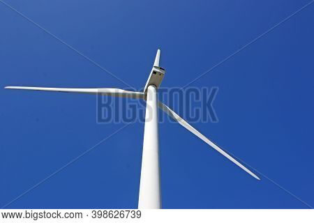Looking Up A Wind Turbine Against A Blue Sky