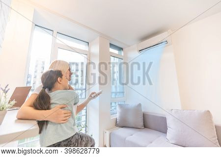 Mother In Sportswear With Daughter Standing Near The Air Conditioning