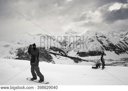 Group Of Snowboarders Starts On Off-piste Descent. High Snowy Mountains And Cloudy Storm Sky At Wint