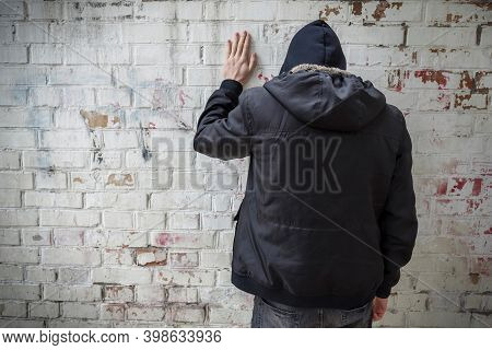 A Man In A Hood Experiencing A Crisis Of Dependence Against A Brick Wall. The View From The Back. Ad