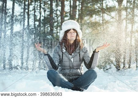 Young Woman With Closed Eyes Meditates In Winter Forest During Snowfall. Tranquility And Concentrati