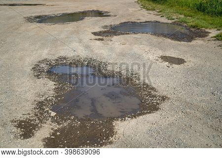 Potholes On A Gravel Dirt Road, Filled With Water