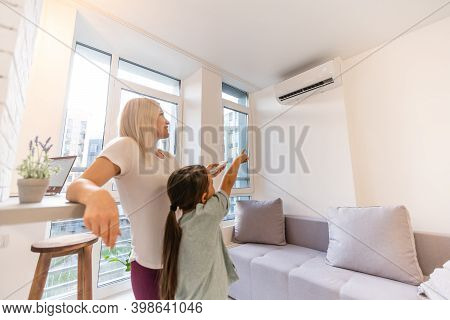 Happy Family Under Air Conditioner, Mom Holding Remote Control Switch On Conditioning In Living Room