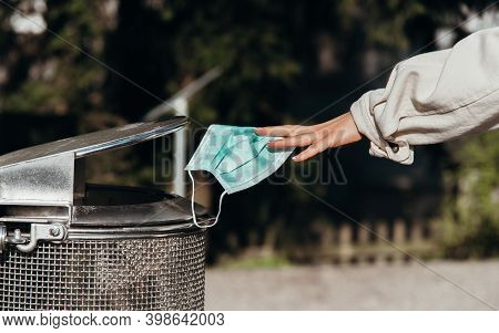 Person Throws A Protective Mask Into The Trash Can\nperson Throws A Protective Mask Into The Trash C