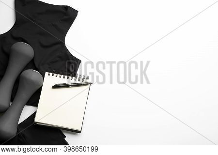Sportswear, Notebook And Dumbbells On White Background, Flat Lay. Gym Workout Plan