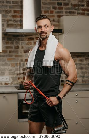 A Smiling Muscular Man With A White Towel On The Shoulders Is Posing With Pull Elastic Rope In His A