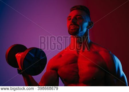 A Close Photo Of A Muscular Man With A Beard Who Is Doing Bicep Curls With Dumbbells Under Blue And