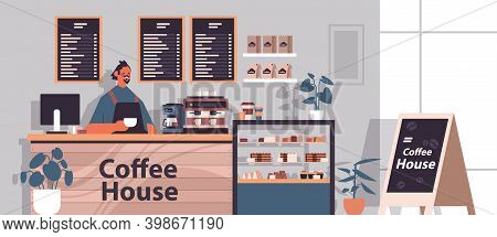 Male Barista In Uniform Working In Modern Coffee House Waiter In Apron Standing At Cafe Counter Hori