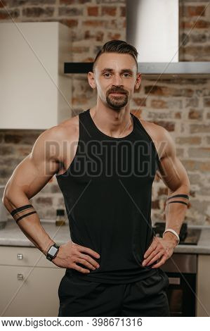 A Muscular Man With A Beard Is Posing In His Apartment After A Workout. The Athletic Guy Is Demonstr