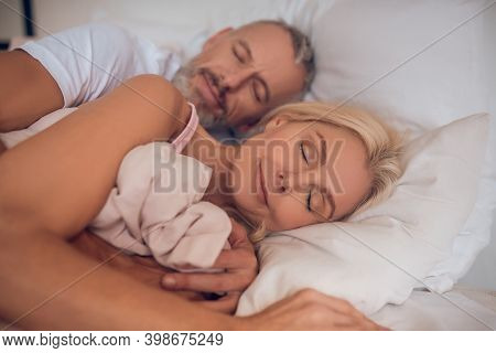 Mature Couple Sleeping On A Bed Together