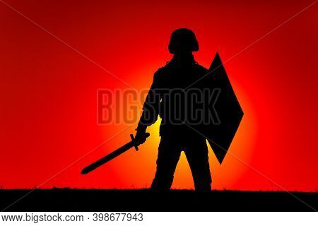 Silhouette Of Modern Soldier In Combat Helmet, Armed Sword And Shield, Standing On Background Of Sun