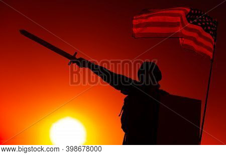 Silhouette Of Usa Army Soldier Standing Under National Flag, Holding Shield, Raising And Pointing Sw