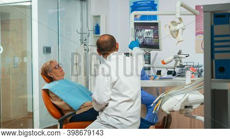 Dentist Asking For Dental Radiography During Patient Consultation. Orthodontist And Nurse Working To