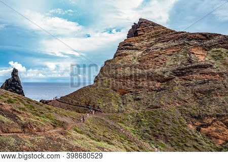 View Of Man Hiking On Rocky Cliff Clear Water Of Atlantic Ocean At Ponta De Sao Lourenco, The Island