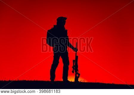 Silhouette Of Army Special Forces Sniper Standing With Rifle On Background Of Sunset Sky. Commando F