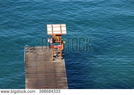 Empty Wooden Pier With Lifeguard Post In Azure Sea, Aerial View. Beach Vacation, Swimming And Water