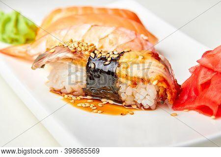 Nigiri Sushi With Smoked Eel, Unagi Sauce And Roasted Sesame Seeds. Close-up, Selective Focus
