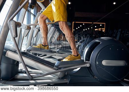 Male Athlete Using The Elliptical Trainer At The Gym