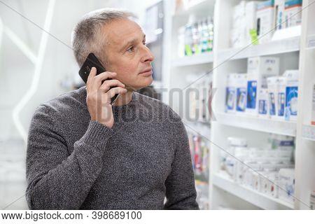 Mature Man Using His Smart Phone, While Shopping At The Drugstore. Senior Male Customer Buying Medic