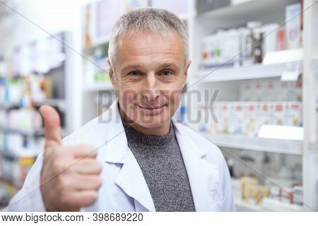 Cheerful Senior Pharmacist Smiling Joyfully, Showing Thumbs Up, Copy Space. Happy Mature Male Chemis