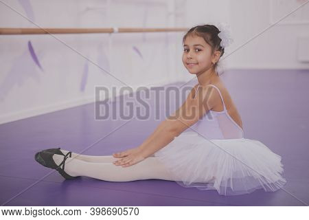 Adorbale Little Ballerina Sitting On The Floor, Resting After Ballet Class, Smiling To The Camera. C