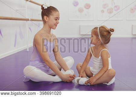 Two Adorable Little Ballerinas Smiling At Each Other, Sitting On The Floor, Resting After Dancing. C