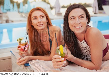 Lovely Young Women Smiling Cheerfully, Sunbathing Near The Swimming Pool Together. Happy Beautiful F