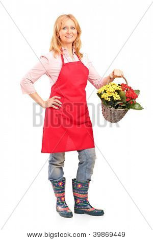 Full length portrait of a mature florist holding a basket full of flowers isolated on white background