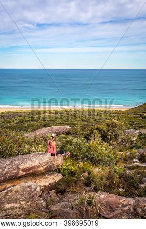 Female Sitting On Rocks In Active Wear With Views Out To Beach And Ocean