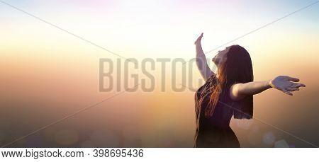 Worship God Concept: Happy Girl Raised Hand On Blurred Mountain Sunrise Background. Ai Yerweng, Beth