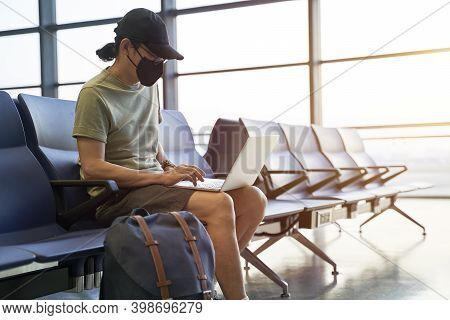 Asian Man Male Air Traveler With Black Face Mask Sitting In Emply Waiting Area In Airport Terminal B