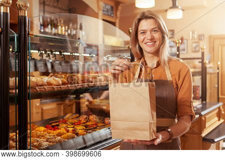 Happy Mature Female Baker Smiling, Holding Out Paper Shopping Bag To The Camera, Selling Delicious B