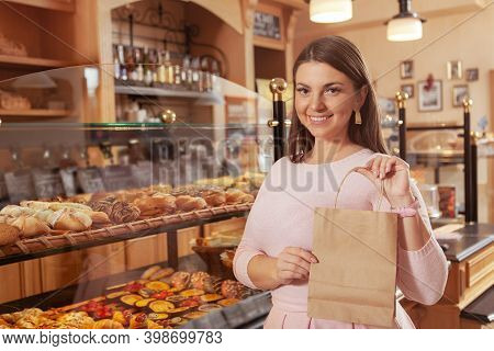 Attractive Plus Size Woman Smiling To The Camera, Holding Paper Shopping Bag, Copy Space. Happy Woma